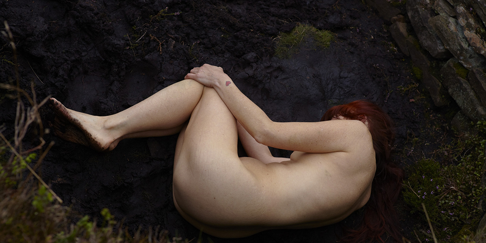 A woman lies in a foetal position in the landscape